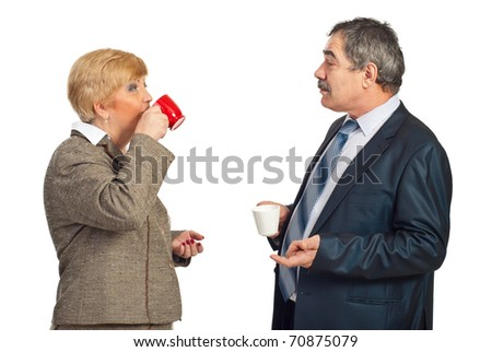 Two mature business people drinking coffee in a business break and having conversation together isolated on white background - stock photo