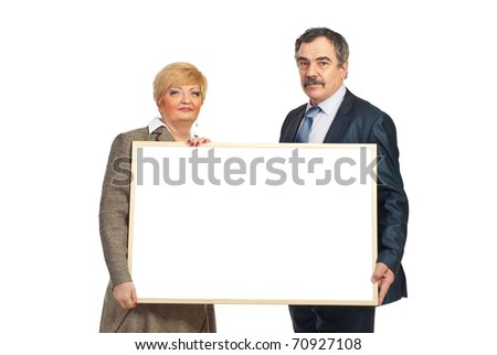 Two mature business people holding a blank banner isolated on white background - stock photo
