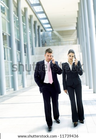Two mature businesspeople walking and calling on mobilephone in downtown district. - stock photo