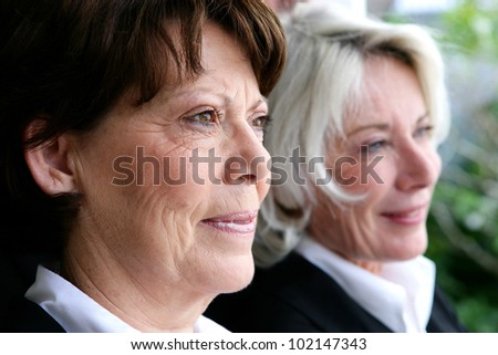 two mature businesswomen posing together - stock photo