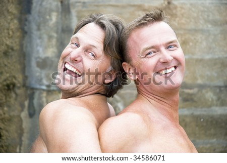 Two mature gay men are laughing and fooling around together. - stock photo