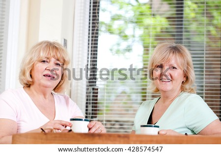 Two mature girlfriends are talking over a cup of coffee. - stock photo