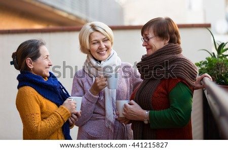 Two mature women drinking tea on a balcony and smiling - stock photo