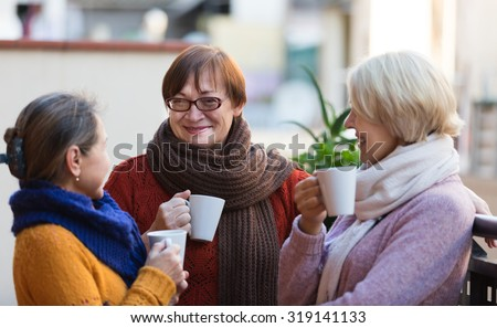 Two mature women drinking tea on balcony and smiling - stock photo