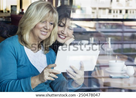 Two mature women sitting in cafe and using a digital tablet.  Shot through the window.  - stock photo