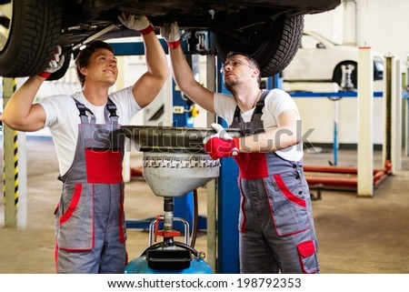 Two mechanic changing oil  in a car workshop - stock photo