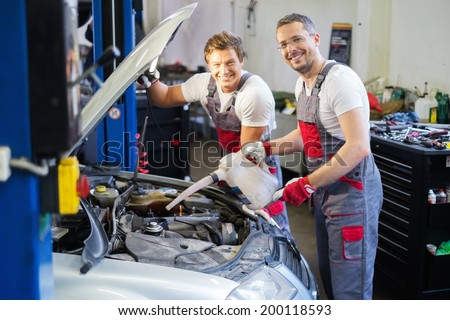 Two mechanics adding oil level in a car workshop - stock photo
