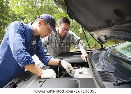 two Mechanics  fixing the car on the road - stock photo