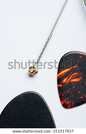 Two mediators with electric guitar string on a white surface - stock photo