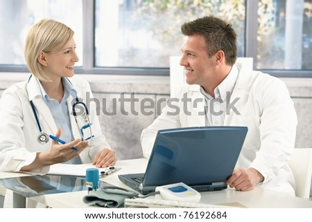 Two medical doctors consulting, smiling at office desk.? - stock photo