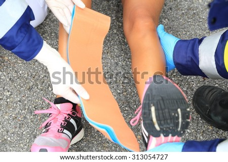 Two Medics helping a female runner with a hurt ankle - stock photo