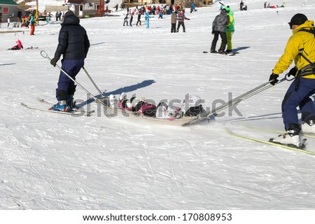 Two members of a ski patrol helping an injured skier down the mountain - stock photo