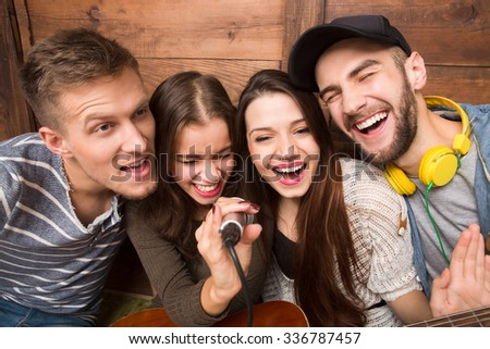Two men and two ladies spending their free time in karaoke. Modern people singing songs and happy smiling for the camera. - stock photo