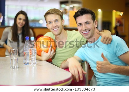 Two men and woman with balls sit at table in bowling and men thumb up; two bottles and glass with water on table; focus on right man; shallow depth of field - stock photo