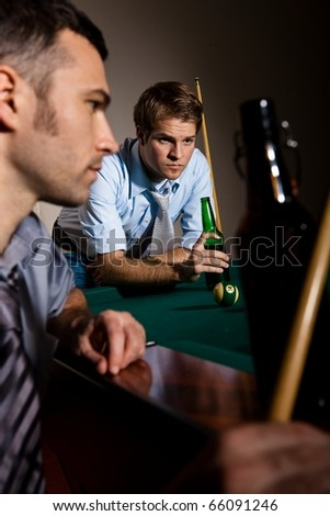 Two men concentrating on playing snooker, drinking beer at game.? - stock photo