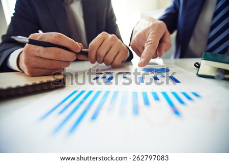 Two men discussing diagram - stock photo