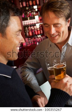 Two Men Enjoying Drink Together In Bar - stock photo