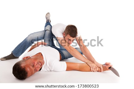 Two men fighting on the ground for a knife - stock photo