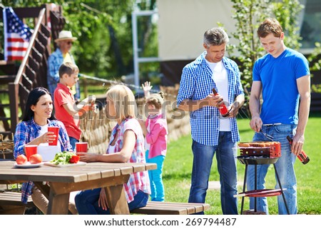 Two men frying sausages on grill outdoors with young women talking by table near by - stock photo