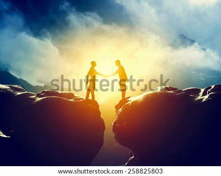 Two men handshake over mountains precipice. Business, deal, connection concepts - stock photo