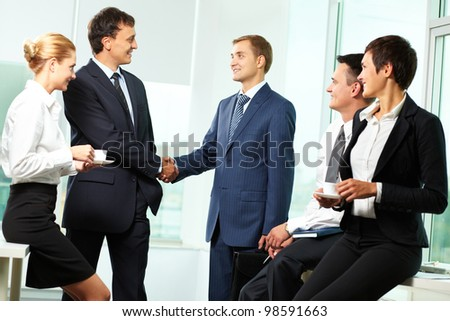 Two men handshaking while other business partners looking at them - stock photo