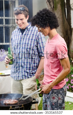 Two men having beers by the barbeque at a party, with meat on the smoking grill - stock photo