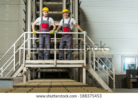 Two men in a safety hats on a factory   - stock photo