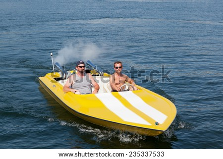 Two men in a yellow and white speedboat having fun in the sunshine. - stock photo