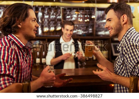 Two men in casual clothes are talking and drinking beer while sitting at bar counter in pub, a bartender in the background - stock photo