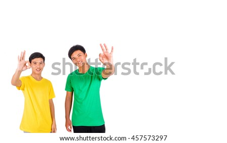 Two men in green and yellow shirt show OK sign with their fingers - stock photo