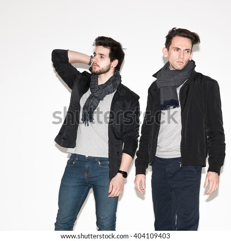 two men in jackets posing in the studio. fashionable young attractive guys - stock photo