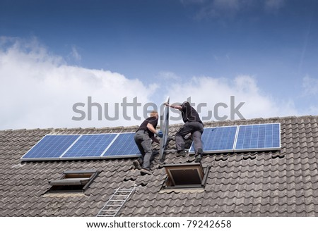 two men installing solar panels on rooftop - stock photo