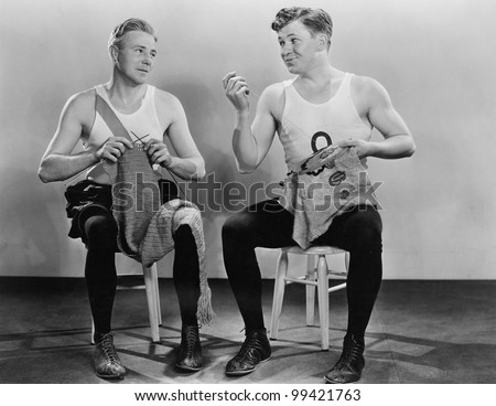 Two men knitting and sewing - stock photo