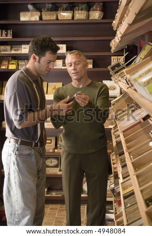 Two men looking at boxes of cigars - stock photo