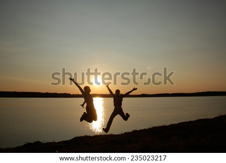 Two men on the lake.Portrait of a sunset in the background - stock photo