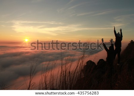 Two men on top of mountain in fog. Conceptual design.low key lighting .Silhouette .Selective focus. - stock photo