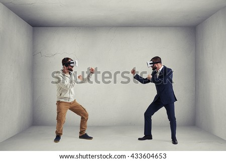 Two men, one in casual clothes, another in dark business suit, are wearing virtual reality glasses and standing in fighting poses ready to start their combat in virtual reality in room - stock photo