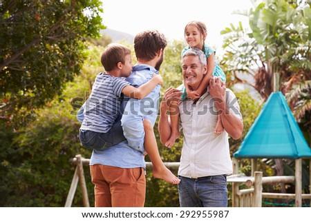Two men piggybacking kids in a garden - stock photo