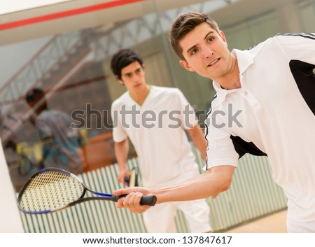 Two men playing a match of squash - stock photo