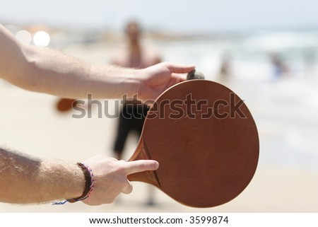 Two men playing beach tennis on the beach - stock photo