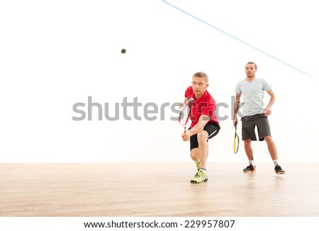 Two men playing match of squash. Squash players in action on squash court  - stock photo
