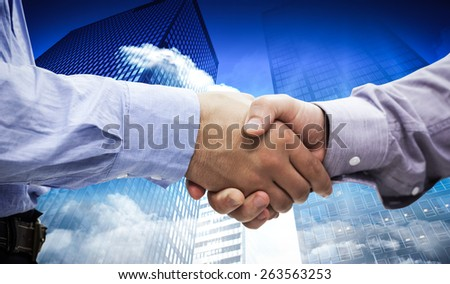 Two men shaking hands against low angle view of skyscrapers - stock photo