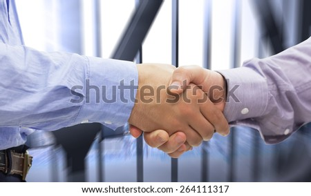 Two men shaking hands against room with large window looking on city - stock photo