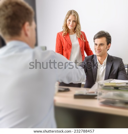 Two men shaking hands in an office and a woman supervising - stock photo