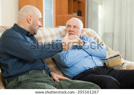 Two men siting on  couch and talking  - stock photo
