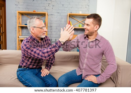 Two men sitting on couch and  giving a high five to each other - stock photo