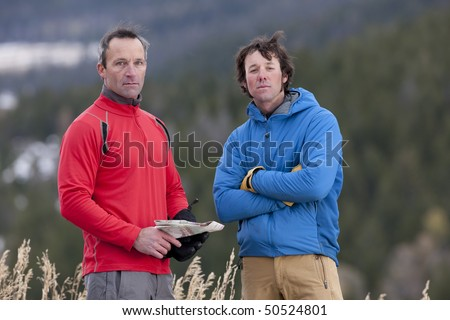 Two men stand together in the wilderness and look at the camera with serious expressions. One is holding a map. Horizontal format. - stock photo
