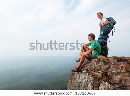 Two men standing on top of a mountain with backpacks - stock photo
