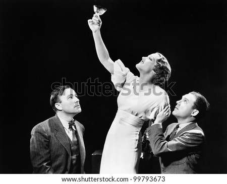 Two men supporting  a woman lifting her wine glass - stock photo