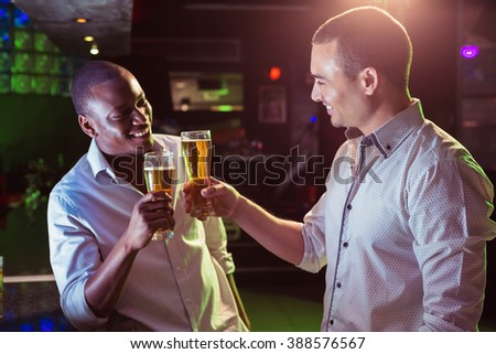 Two men toasting with glass of beer in bar - stock photo